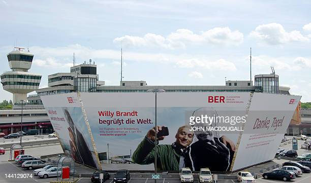 A giant billboard advertises Berlin's new Willy Brandt Berlin Brandenburg International airport at Berlin's Tegel airport May 10 2012 The scheduled...