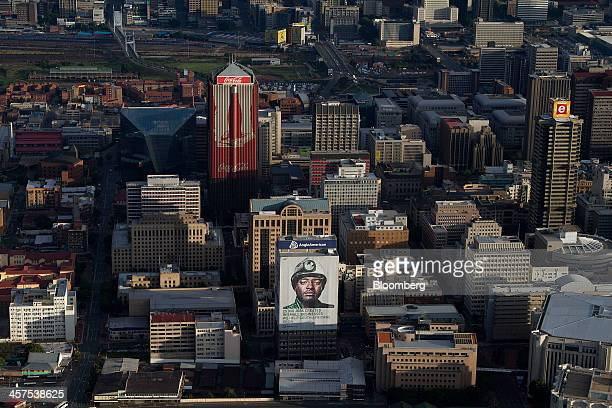 A giant billboard of a miner hangs on the side of the Anglo American Plc offices below center near a CocaCola Co advertisement on the Southern Life...