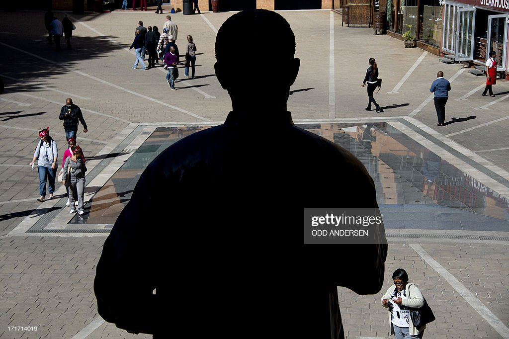 A giant bronze statue of Nelson Mandela is silhouetted as people walks across Nelson Mandela square in the north Johannesburg suburb of Sandton on June 28, 2013. Mandela is receiving treatment at the Mediclinic heart hospital in Pretoria. Mandela's close family gathered yesterday at his rural homestead to discuss the failing health of the South African anti-apartheid icon who was fighting for his life in hospital. Messages of support poured in from around the world for the Nobel Peace Prize winner, who spent 27 years behind bars for his struggle under white minority rule and went on to become South Africa's first black president.