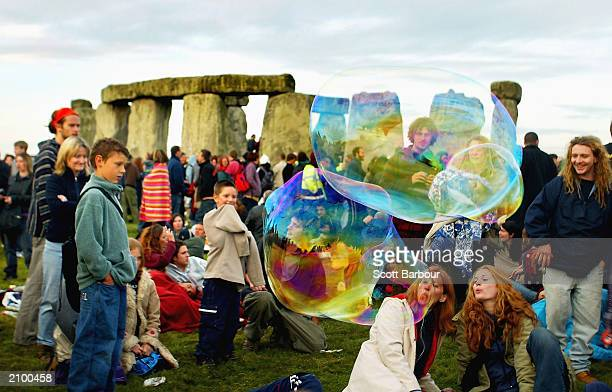 A giant bubble floats through the air as revellers greet the sun rising above Stonehenge on the day of the Summer Solstice June 21 2003 in Wiltshire...