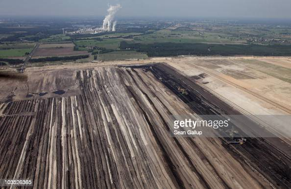 Giant bucketwheel excavators and a conveyor bridge operate in the Jaenschwalde openpit lignite coal mine next to rows of conveyed soil on August 20...