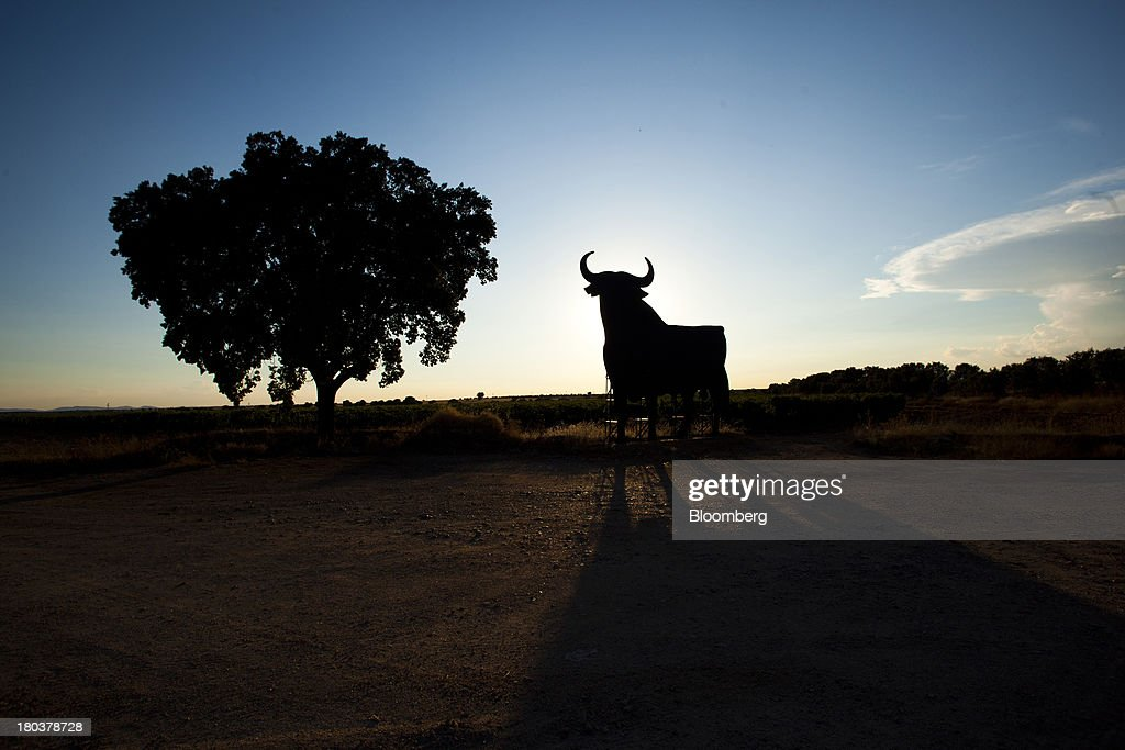 A giant bull advertisement for the Bodegas Osborne SA winery stands on display by a roadside at the company's vineyards in Malpica de Tajo, Spain, on Wednesday, Sept. 11, 2013. Spanish manufacturing expanded in August for the first time in more than two years, strengthening Prime Minister Mariano Rajoy's prediction that exports will help the economy emerge from recession this year. Photographer: Angel Navarrete/Bloomberg via Getty Images