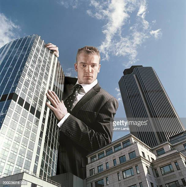 Giant businessman looking over office buildings, low angle view