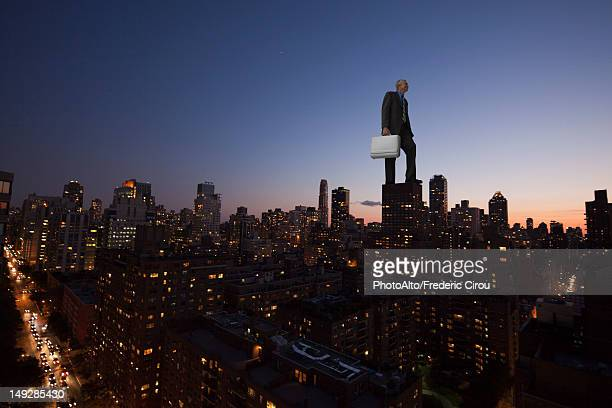 Giant businessman standing on top of skyscraper at dusk