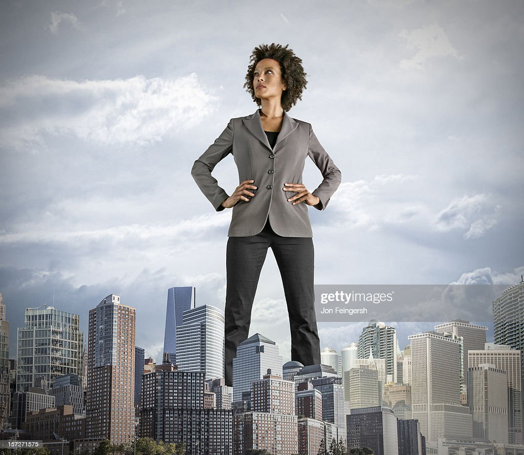 Giant Businesswoman stands in the middle of a city : Stock Photo