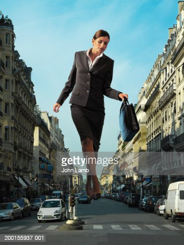 Giant businesswoman walking in middle of city road (Digital Composite)