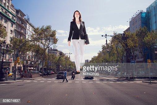Giant businesswoman walking