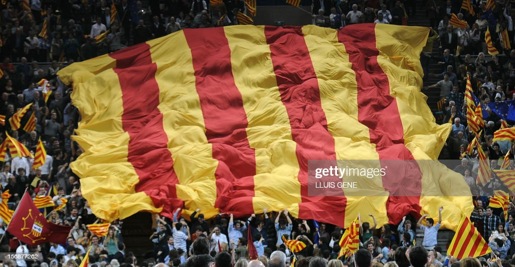 A giant Catalan flag is displayed by supporters of Artur Mas, current President of Catalonia and leader of the CiU (Catalan Convergence and Unity party) during a final meeting for his re-election campaign on November 23, 2012, in Barcelona. Artur Mas is seeking re-election in the upcoming Catalonia regional elections on November 25 and promised voters a referendum on the 'independance' and 'auto-determination' of the region if he wins a new mandate. AFP PHOTO/ LLUIS GENE