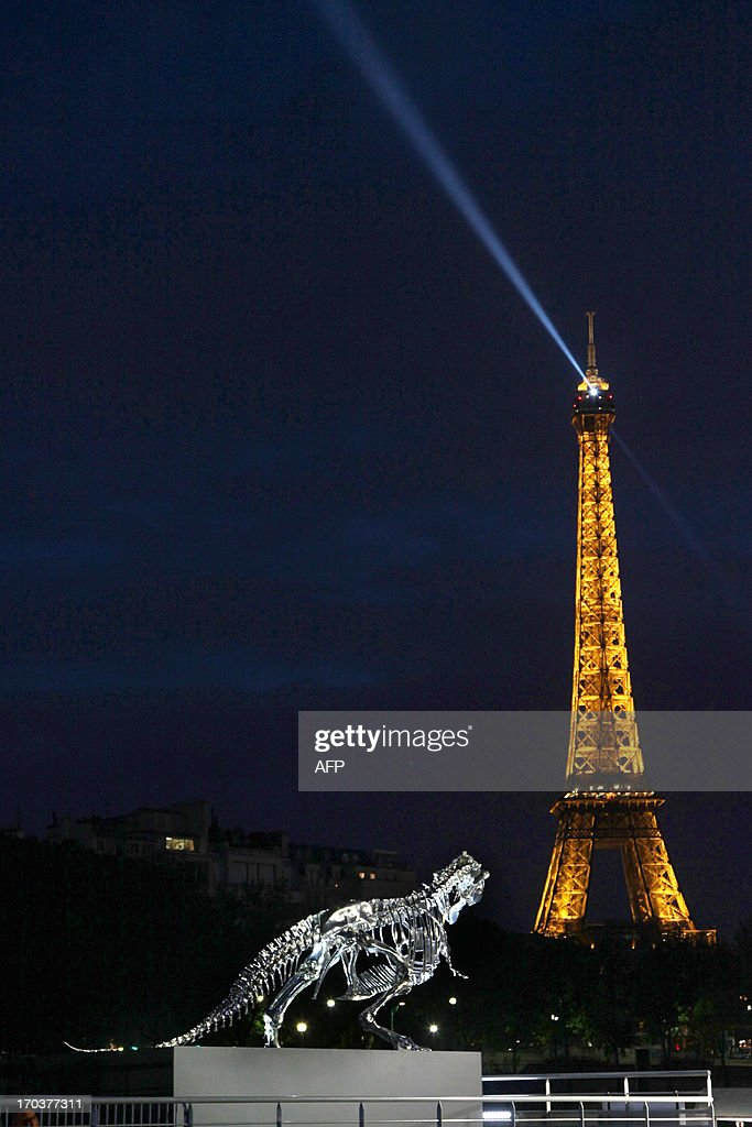 A giant chrome brushed aluminium skeleton of a Tyrannosaurus (T-Rex) dinosaur (L), made by French sculptor and painter Philippe Pasqua, stands at the pier of riverboat company Bateaux-Mouches on June 12, 2013 in Paris, with the Eiffel tower in the background (R).