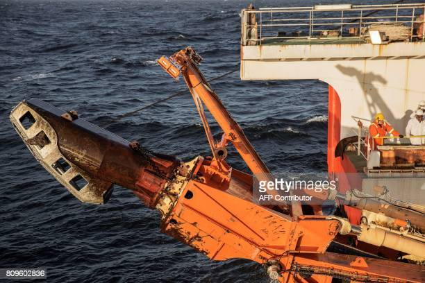A giant crawler machine used to dredge the seabed for diamonds is seen being pulled on board the Diamonds Sea Mining vessel MAFUTA from Debmarine a...