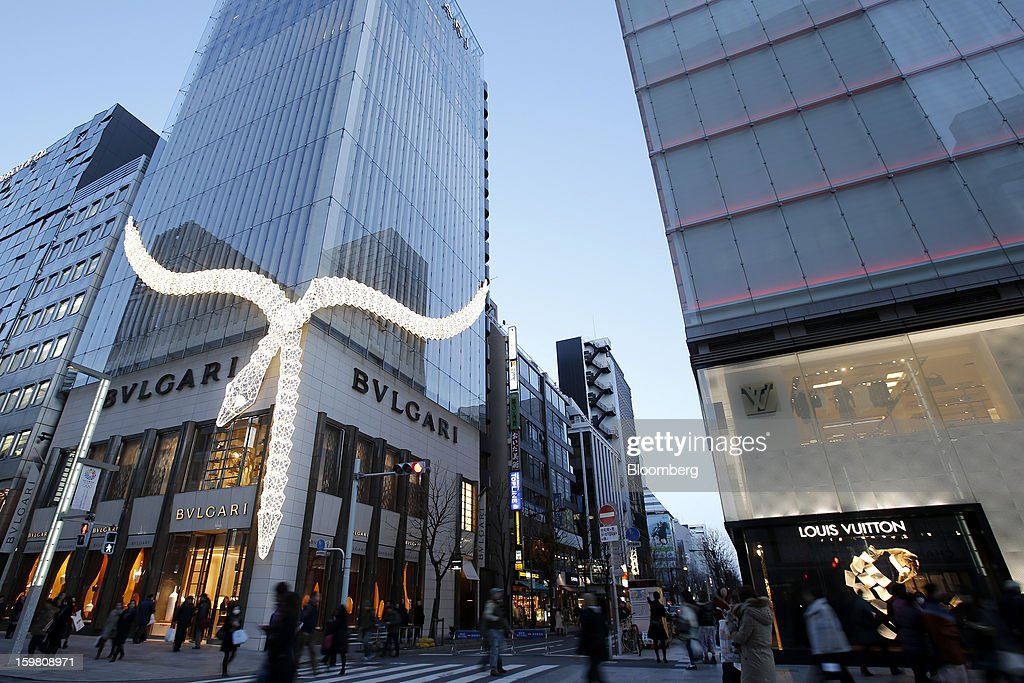 A giant display snake is illuminated on the exterior of the Bulgari SpA store, a luxury unit of LVMH Moet Hennessy Louis Vuitton SA, left, as a Louis Vuitton store stands opposite in the Ginza district of Tokyo, Japan, on Sunday, Jan. 20, 2013. Japan's consumer prices excluding fresh food, a benchmark monitored by the central bank, haven't advanced 2 percent for any year since 1997, when a national sales tax was increased. Photographer: Kiyoshi Ota/Bloomberg via Getty Images