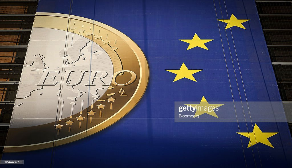 A giant euro banner, featuring an image of a euro coin and promoting stronger European economic governance, hangs on the side of the headquarters of the European Union commission at the Berlaymont Building, in Brussels, Belgium on Monday Nov. 21, 2011. Germany is signaling resistance to stepping up Europe's response as the debt crisis that began more than two years ago in Greece threatens France, after snaring Ireland, Portugal, Italy and Spain. Photographer: Jock Fistick/Bloomberg via Getty Images