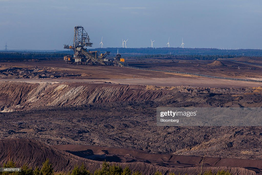 A giant excavator collects lignite, also known as brown coal, from the open-pit mine operated by Vattenfall AB as wind turbines stand on the horizon, in Welzow-Sued, Germany, on Saturday, Jan. 11, 2014. Across the continent's mining belt, from Germany to Poland and the Czech Republic, utilities such as Vattenfall AB, CEZ AS and PGE SA are expanding open-pit mines that produce lignite. Photographer: Krisztian Bocsi/Bloomberg via Getty Images