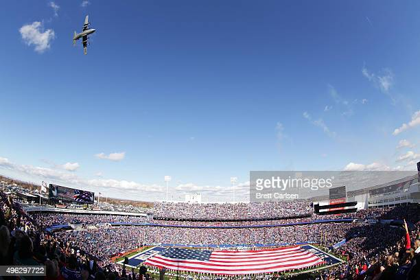 A giant flag covers the field as a C130 flies overhead during pregame ceremonies before the Miami Dolphins and the Buffalo Bills football game at...
