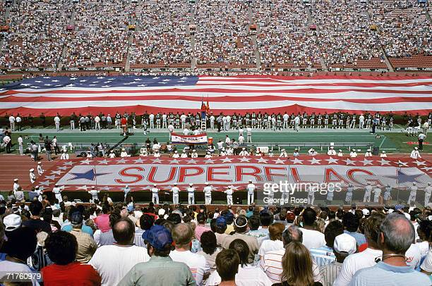 A giant flag is display on the field during the National Anthem before a game with the Detroit Lions against the Los Angeles Raiders at Los Angeles...
