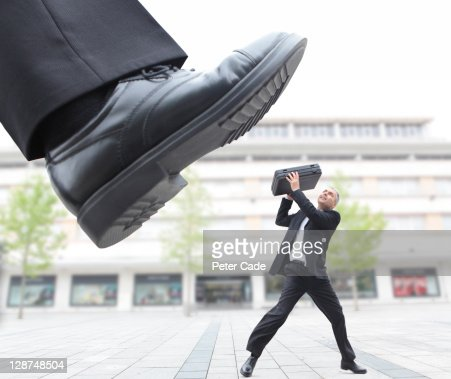 giant foot stepping on male executive