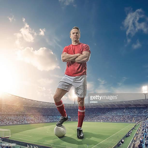 Giant Footballer Standing in Floodlit Soccer Stadium At Sunset