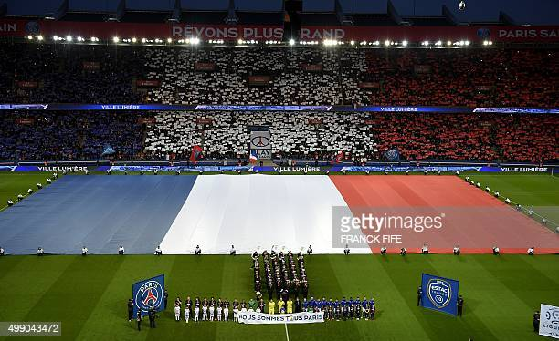 A giant French flag covers the pitch as spectators and players holding a banner 'We are all Paris' observe a minute of silence for the victims of the...