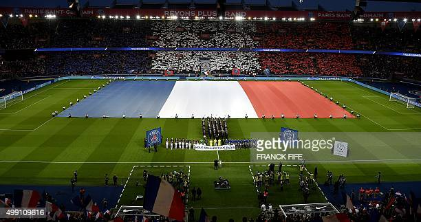 A giant French national flag covers the pitch as players and spectators observe a minute of silence for the victims of the November 13 terror attacks...