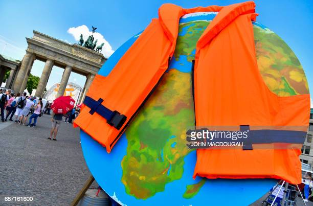 A giant globe is dressed with a lifejacket during a protest by environmental activists from Greenpeace outside the venue of the 8th Petersberg...
