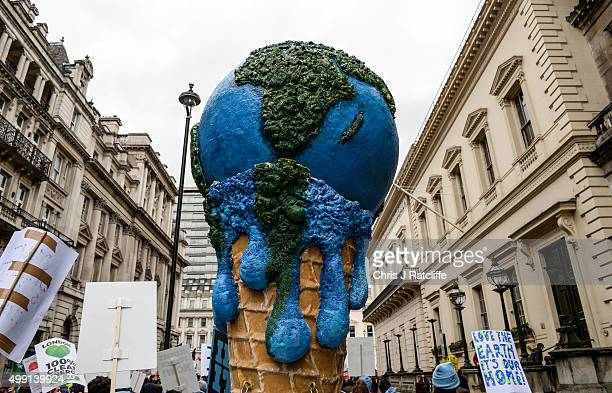 A giant globe shaped ice crem melts over a cone during the London Climate March as part of march events around the globe on the same day on November...