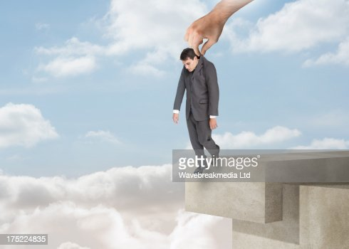Giant hand dropping off a businessman over the clouds : Stock Photo