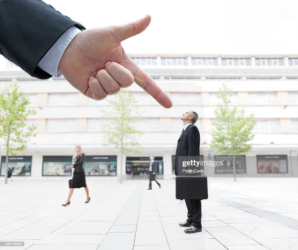 giant hand pointing at male executive in street : Stock Photo