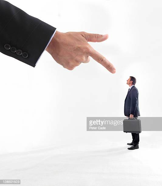 Giant hand pointing at male executive