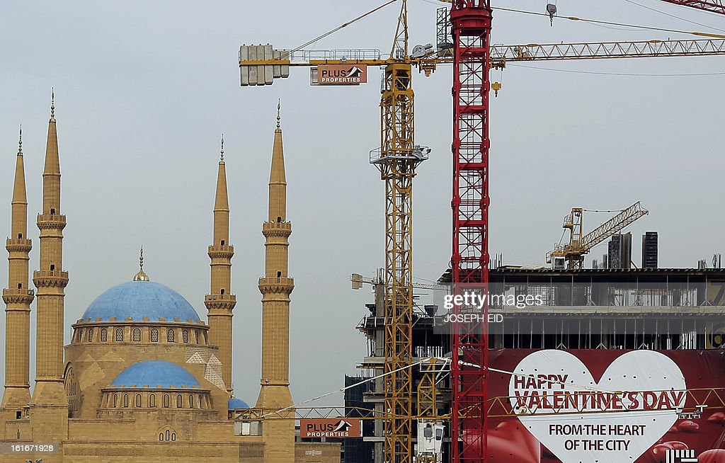 A giant happy Valentine's day poster hangs on a construction site near a mosque in downtown Beirut on February 14, 2013. Valentine's Day is increasingly popular in the region as people have taken up the custom of giving flowers, cards, chocolates and gifts to sweethearts to celebrate the occasion. AFP PHOTO/JOSEPH EID