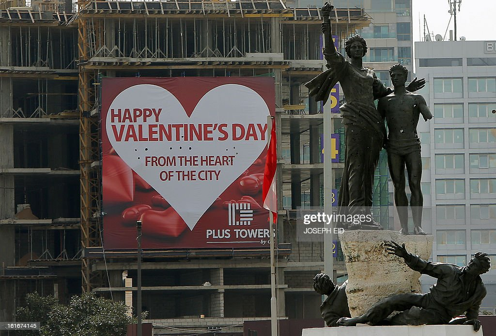 A giant happy Valentine's day poster hangs on a construction site next to central Beirut's Martyrs Statue on February 14, 2013. Valentine's Day coincides in Lebanon with the anniversary of the assassination of former premier Rafiq Hariri who was murdered in a massive car bomb attack that killed him along with 21 others while driving through the Lebanese capital on February 14, 2005.