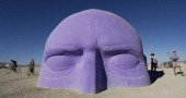 DESERT NV A giant head one of many art installlations dotting the playa at Burning Man appears to emerge from the sand About 35000 are expected to...