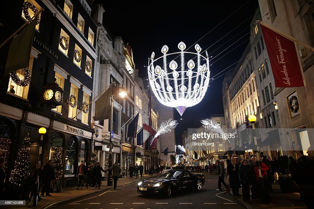 Giant illuminated festive decorations hang above pedestrians and a luxury automobile outside a Tiffany Co store on Old Bond Street in London UK on...