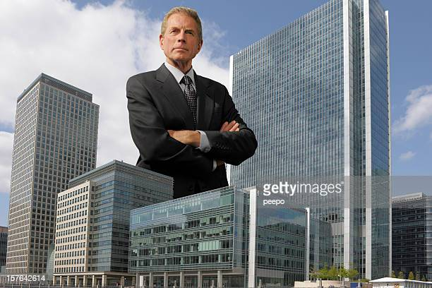 giant man in a suit stands beside two skyscrapers