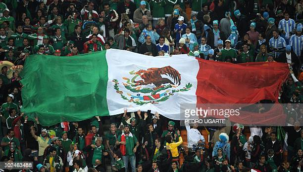 A giant Mexican flag is held by supporters prior to the 2010 World Cup round of 16 match Argentina vs Mexico on June 27 2010 at Soccer City in Soweto...