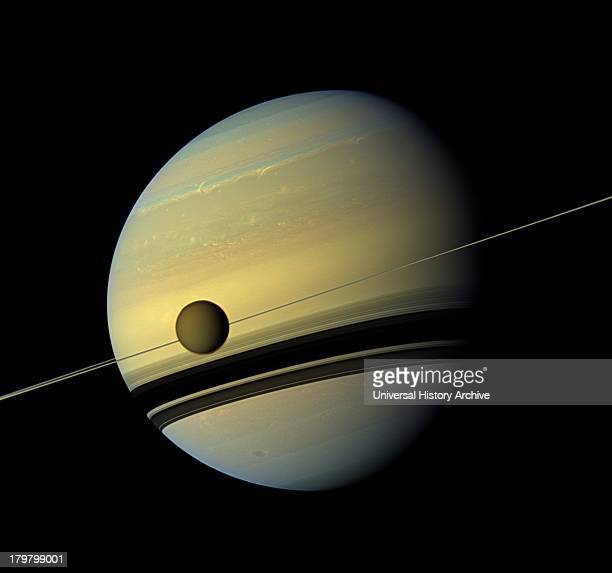 A giant of a moon appears before a giant of a planet undergoing seasonal changes in this natural color view of Titan and Saturn from NASA's Cassini...