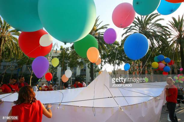 A giant paper boat floats in the air with the help of helium balloons in front of the Arc de Triomphe in Barcelona on July 17 2008 during the...