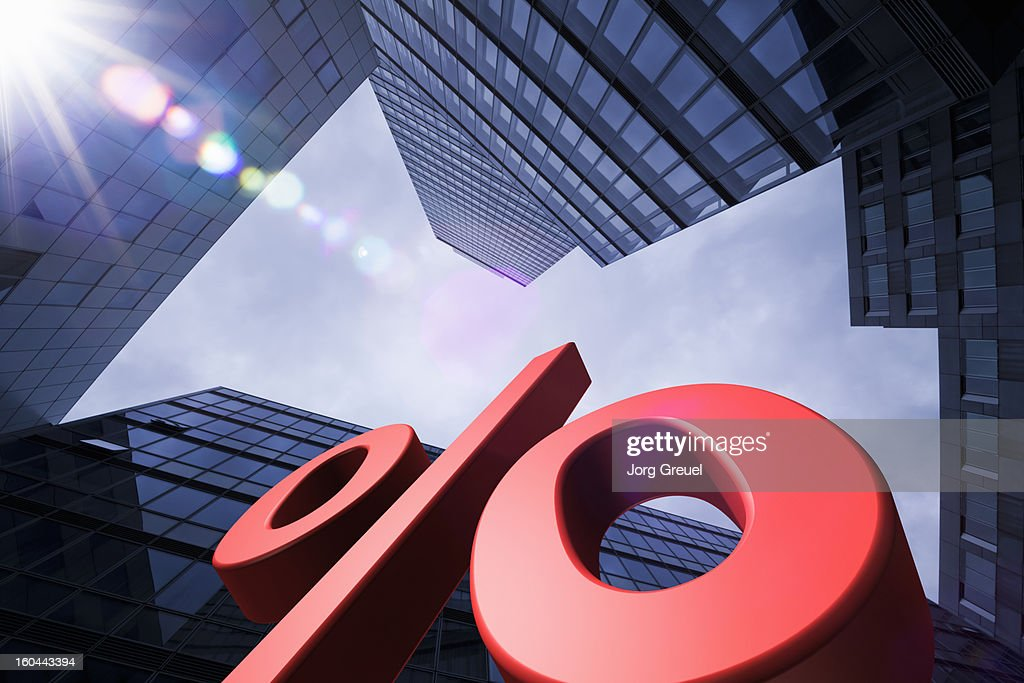 Giant percent sign and office buildings : Stock Photo