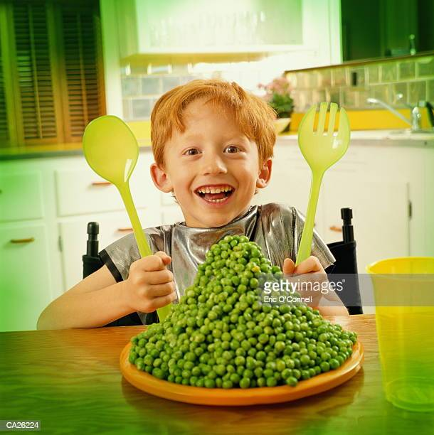 Giant plate of peas in front of boy (7-9) at kitchen table, portrait