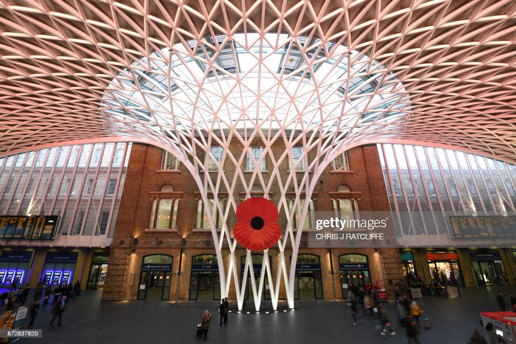 A giant poppy is displayed in the concourse at King's Cross station in central London on November 11, 2017, the Armistice Day. On Armistice Day, many Britons wear a paper red poppy -- symbolising the poppies which grew on French and Belgian battlefields during World War I -- in their lapels. / AFP PHOTO / Chris J Ratcliffe
