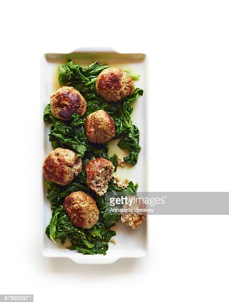 Giant pork meatballs with bitter greens on white
