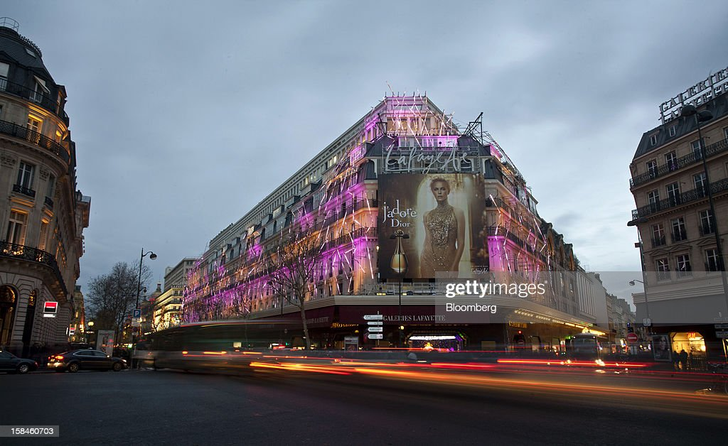 A giant poster advertising Christian Dior SA's Dior perfume sits above the entrance to the illuminated Galeries Lafayette department store in Paris, France, on Saturday, Dec. 15, 2012. The French minister for energy and environment unveiled a proposal for lights in and outside shops, offices, and public buildings -- including the flagship Louis Vuitton store and the Lido cabaret house on Paris's Avenue des Champs Elysees -- to be turned off between 1 a.m. and 7 a.m. starting in July. Photographer: Balint Porneczi/Bloomberg via Getty Images