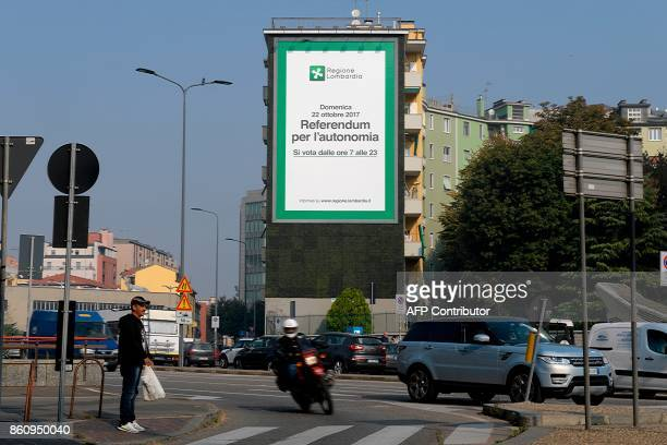 A giant poster announcing a referendum in Italy's northern region of Lombardy to request more autonomy from central government is seen on a building...