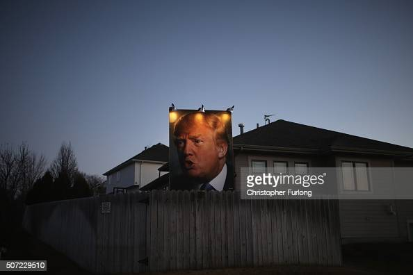 A giant poster of Republican presidential candidate Donald Trump stands in the backyard of a supporter in West Des Moines on January 28 2016 in Des...