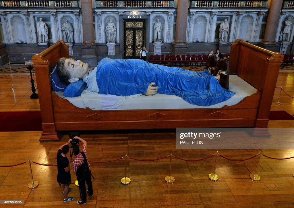 A giant puppet Grandmother is seen lying in a bed in St Georges Hall in Liverpool, north west England on July 23, 2014 ahead of a production by French theatre company Royal de Luxe. The puppets, which visited the city in 2012, return to roam the streets of the city in a three day performance based around memories of August 1914, marking 100 years since the outbreak of the First World War.