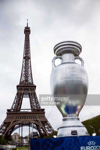 A giant replica of the Henri Delaunay trophy awarded to the winner of the UEFA European Championship is displayed near the Eiffel Tower on the Champs...