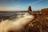 Giant rock and crashing waves seascape