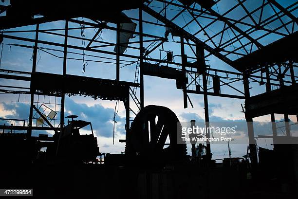 A giant rusty wheel which once squeezed the juice from sugar cane in the Hershey sugar mill is silhouetted against the rising sun on March 30 2015 in...