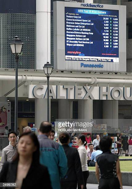 A giant screen showing the Singapore Stock Exchange numbers flashes the latest numbers as workers walk by in Singapore 10 September 2003 Share prices...
