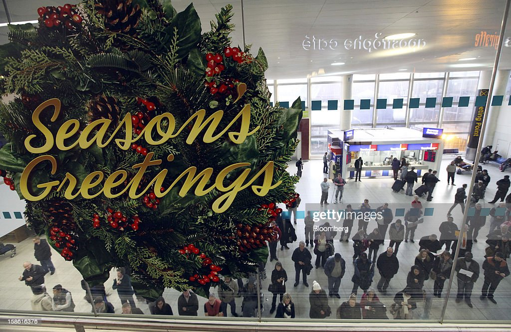 A giant 'Seasons Greetings' wreath hangs on a glass window above the arrivals hall at the south terminal of Gatwick airport in Crawley, U.K., on Friday, Dec. 21, 2012. U.K. airports predicted today to be the busiest day during the Christmas period, as some Britons opt to spend the holidays abroad and overseas visitors fly out to be with friends and family. Photographer: Chris Ratcliffe/Bloomberg via Getty Images