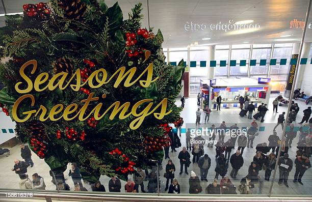 A giant 'Seasons Greetings' wreath hangs on a glass window above the arrivals hall at the south terminal of Gatwick airport in Crawley UK on Friday...